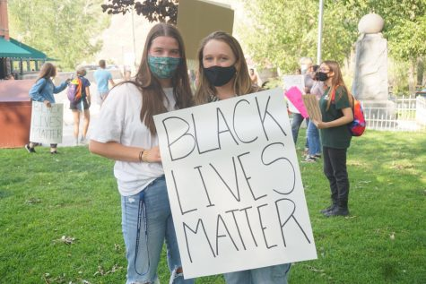 """Seniors Saige Ferguson, left and Norah Blackburn, right show off their BLM poster. All of the students and community members stood peacefully. Though there was some opposition from other Salidans, the protesters didn't engage.   Wierdsma said, """"I had a whole spiel that I gave to everyone and said, 'People get bored. They will leave if we are quiet.' We just didn't engage with them and they left because they got bored and weren't getting anything out of it.""""   The group did as they planned and stayed away from any violence or engagement with others."""